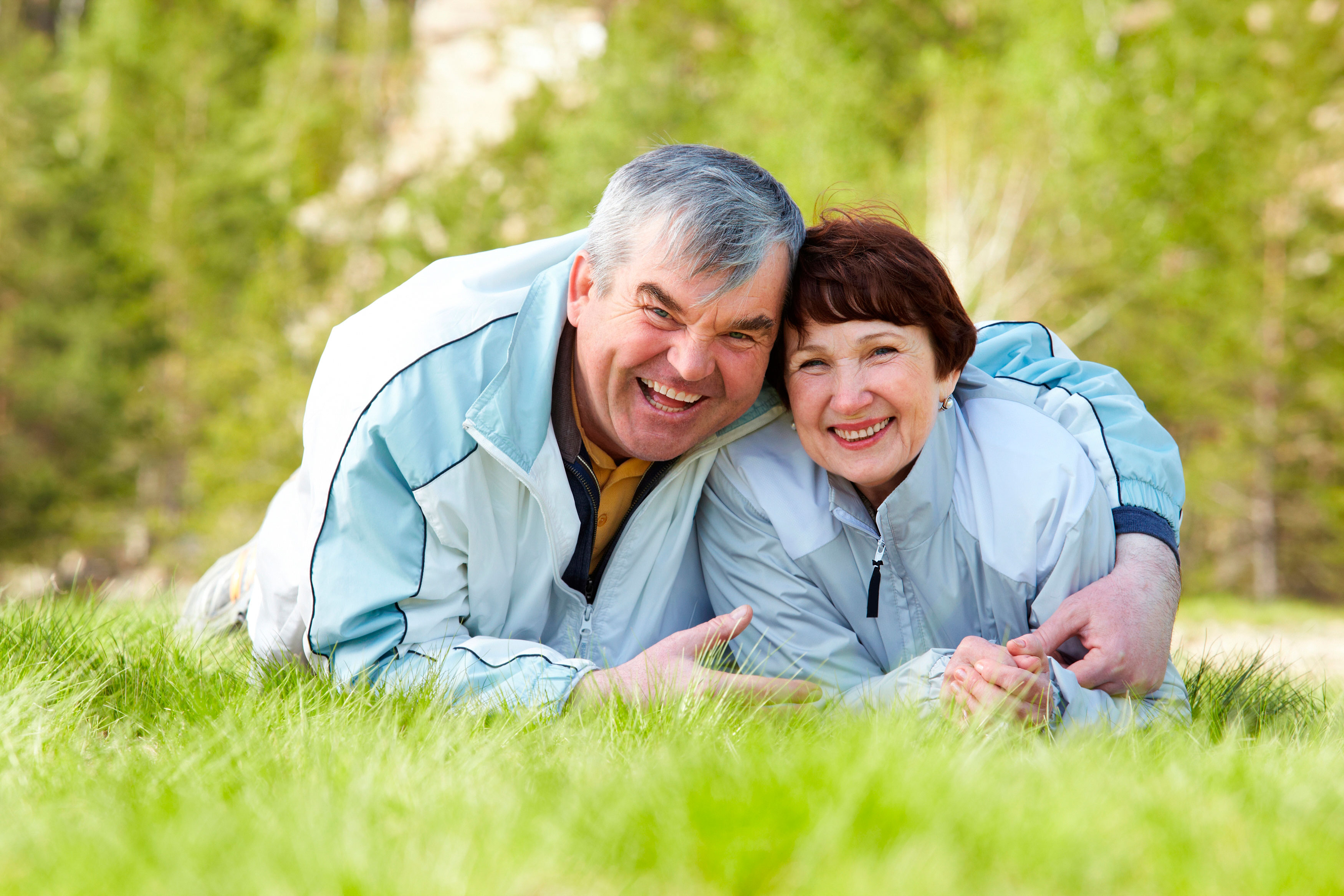 Older man hugs his wife while lying on a grass